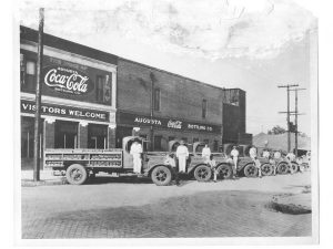 old augusta coca cola factory with trucks parked in front