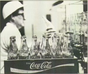 empty glass bottles in a coca cola container with a woman working in the background